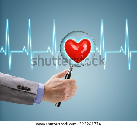 Heart health checkup, doctor with magnifying glass on a heart and ecg diagram - stock photo