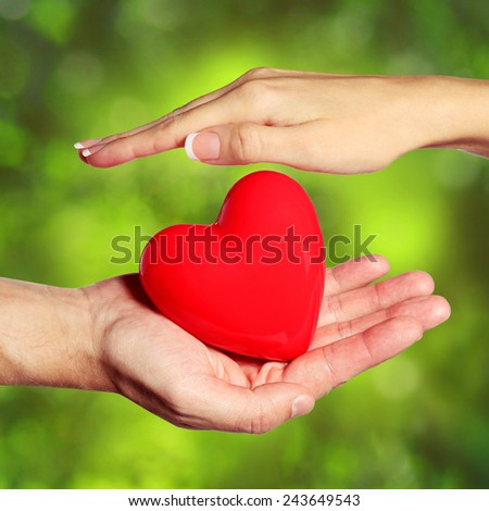 Heart in Female and Male Hands, over Nature Green Background. Love and Relationships Concept