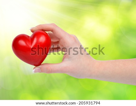 heart in hand on green natural background