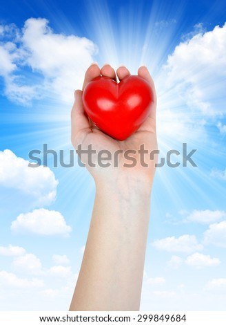 Heart in hand on the background sunny sky - stock photo
