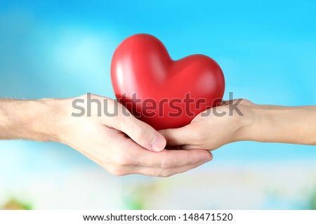Heart in hands on cloud background - stock photo
