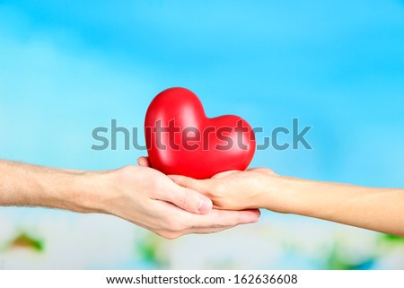 Heart in hands on cloud background