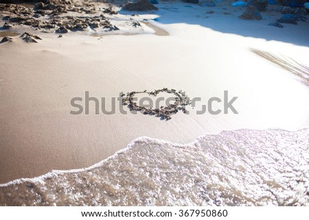heart in sand at the beach, confession of love, summer, sea and sun - stock photo