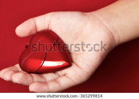 Heart in the hand isolated on red background