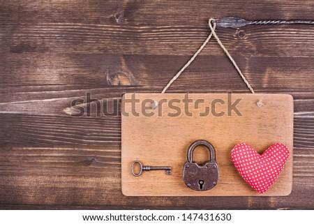 Heart, key, lock on signboard hanging on vintage wood background - stock photo