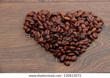 Heart laid out from coffee beans on a wooden background