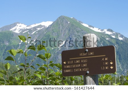 Heart Lake trail marker with snow-capped Bear Mountain in background near Sitka, Alaska on summer day - stock photo