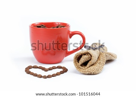 Heart made from coffee beans around a cup of coffee on a white background.