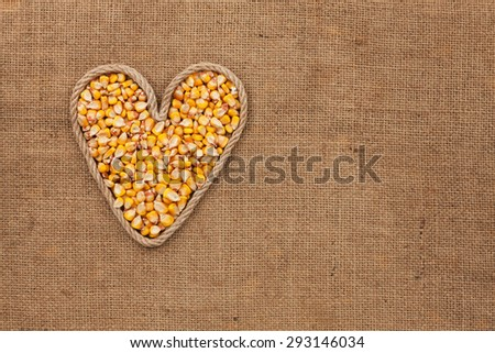 Heart made from rope with corn grains  lying on sackcloth, with space for text - stock photo