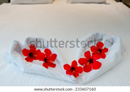 heart made from towels with flowers on honeymoon bed - stock photo