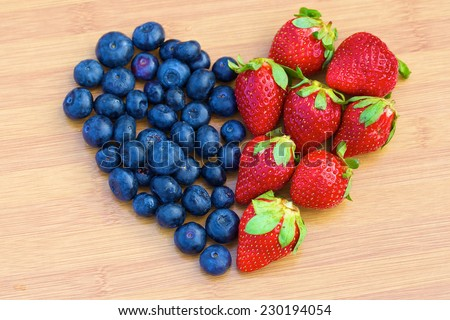 Heart made of blueberries and strawberries on a wooden board - stock photo