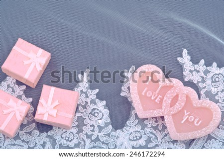 Heart made of candles and pink box on fabric vail background. - stock photo