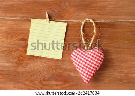 heart made of cloth on wood background with a sheet of yellow paper - stock photo