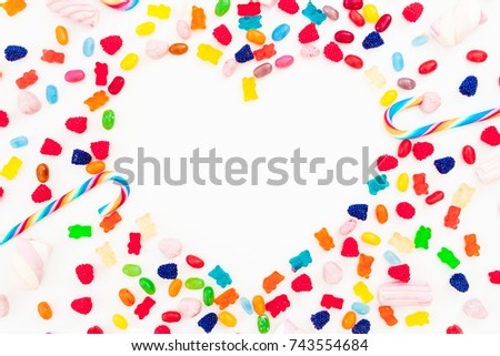 Heart made of colored bright candy isolated on white background. Flat lay, top view