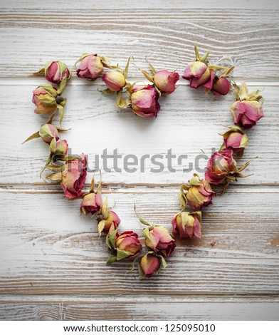 Heart made of dried rose buds - stock photo