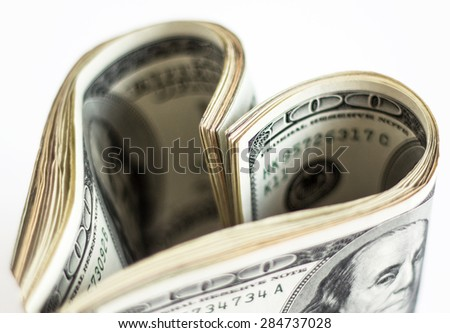 Heart made of few dollar papers. Shallow depth of field. - stock photo
