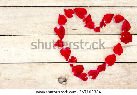 Heart made of red petals on wooden table