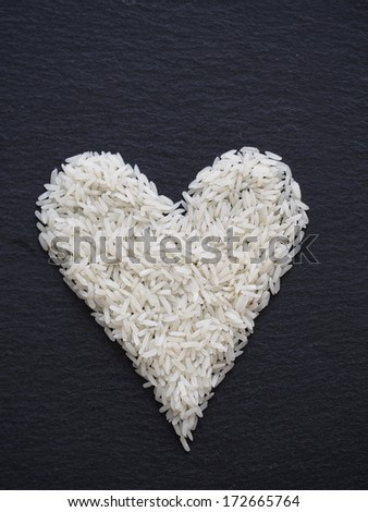 Heart made of rice on a black slate - stock photo