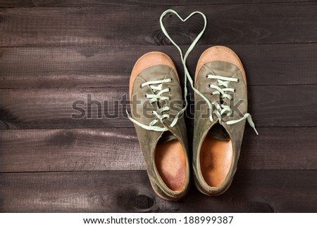 Heart made of shoelaces. Leather green sneakers on black boards