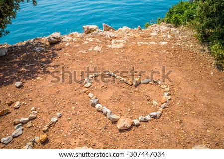 Heart made of stones on the red earth ground on the rocky beach, by the crystal clear blue sea, with some trees and bushes around it, with copy space for text - stock photo