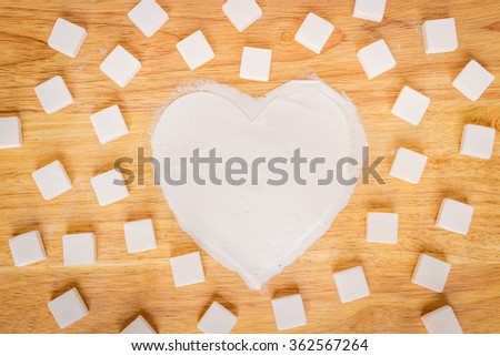 Heart made of sugar on wood background; Valentine's Day, cooking with warm love - stock photo