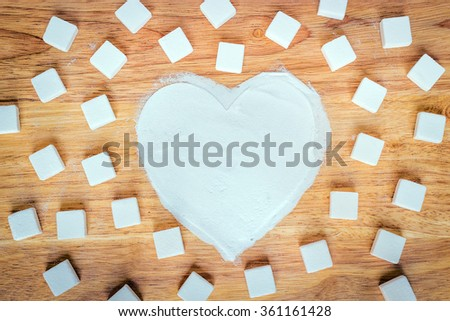 Heart made of sugar on wood background; Valentine's Day, cooking with warm love : vintage tone - stock photo