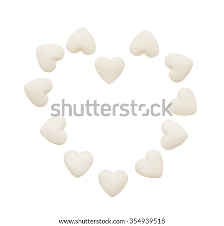Heart made of white heart shape tablets isolated on white background. Clipping path included. - stock photo