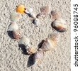 heart made with shells on sand of a beach - stock photo