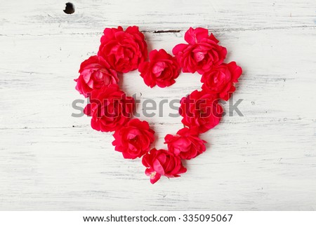 Heart of a red garden roses on white wooden background