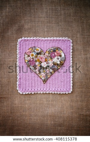Heart of beads on crochet and burlap fabric