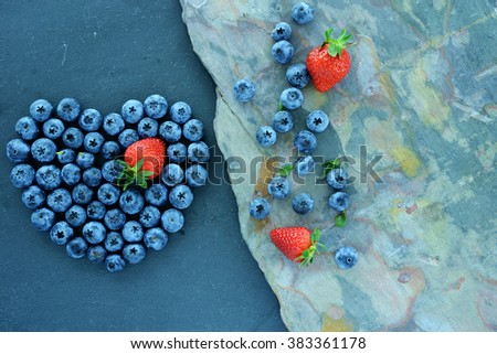 Heart of berries on slate background. Berries on natural stone Background. - stock photo