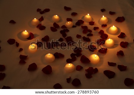 Heart of candles and red petals on bed, close up - stock photo