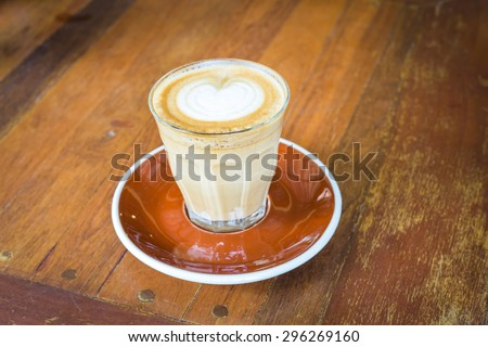 Heart of cappuccino or latte coffee in a clear glass mug on ceramic tray and wood table. - stock photo