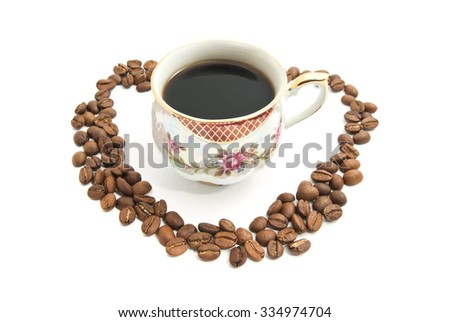 Heart of coffee beans and mug of coffee - stock photo