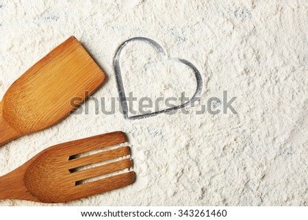 Heart of flour and  wooden kitchen utensils n on gray background - stock photo