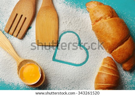 Heart of flour, croissant and  wooden kitchen utensils on color wooden background - stock photo