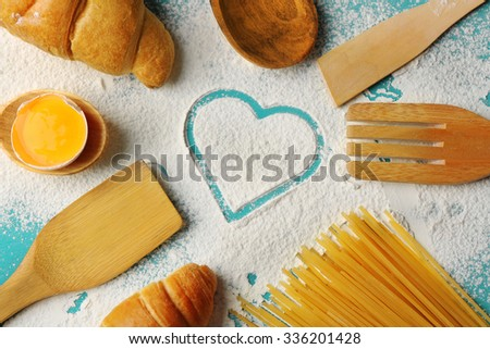 Heart of flour, foodstuffs and kitchen utensils on color wooden background - stock photo