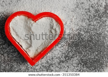 Heart of flour on gray background - stock photo