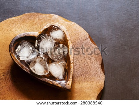 Heart of ice in a wooden bowl, selective focus - stock photo