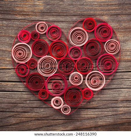Heart of paper quilling on wooden background - stock photo