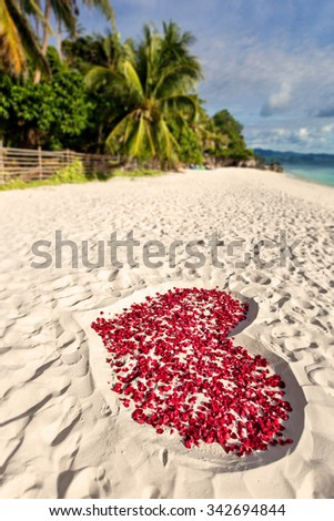 Heart of roses petals on tropical sandy beach. Love concept and romantic card, toned image - stock photo