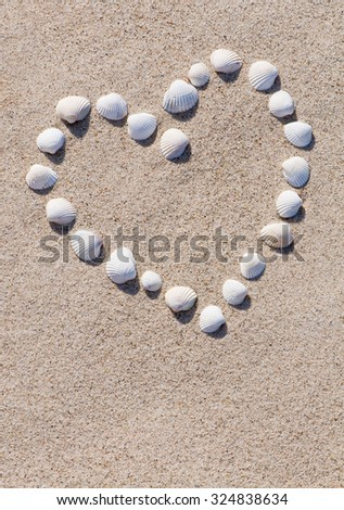 Heart of white shells in the sand; Declaration of love - stock photo