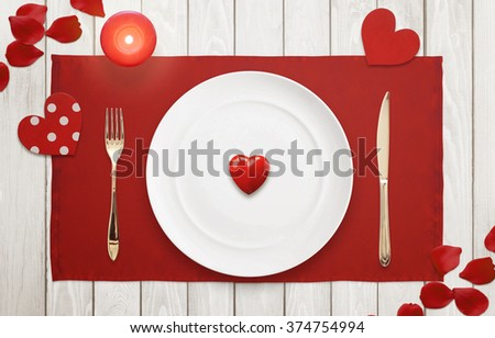 Heart on a plate for dinner. A romantic evening with petals, hearts and candle on wooden table.