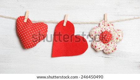 Heart on clothesline on white wooden background
