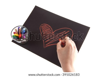 heart on paper on white background, hands and chalk