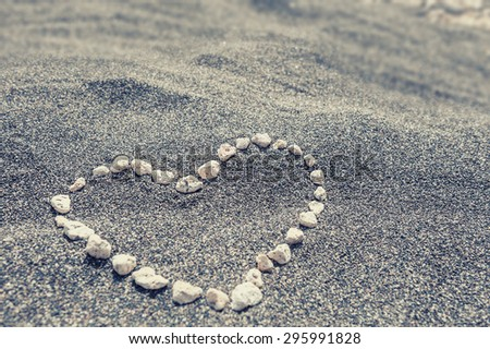 Heart on the black sand. Selective focus. Vintage effect - stock photo