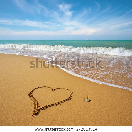Heart on the sand of a beach. Romantic composition. - stock photo