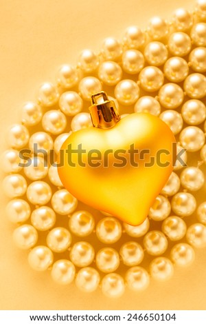 Heart on white pearl necklace in romantic light - stock photo