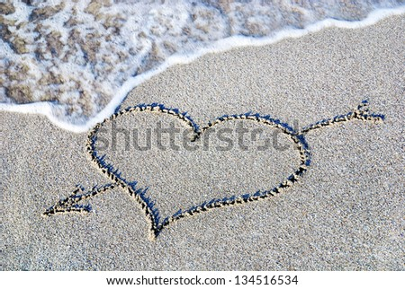 heart outline with arrow on the wet brilliance beach sand against wave