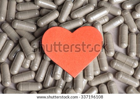 Heart over pills and capsules background, copy space - stock photo